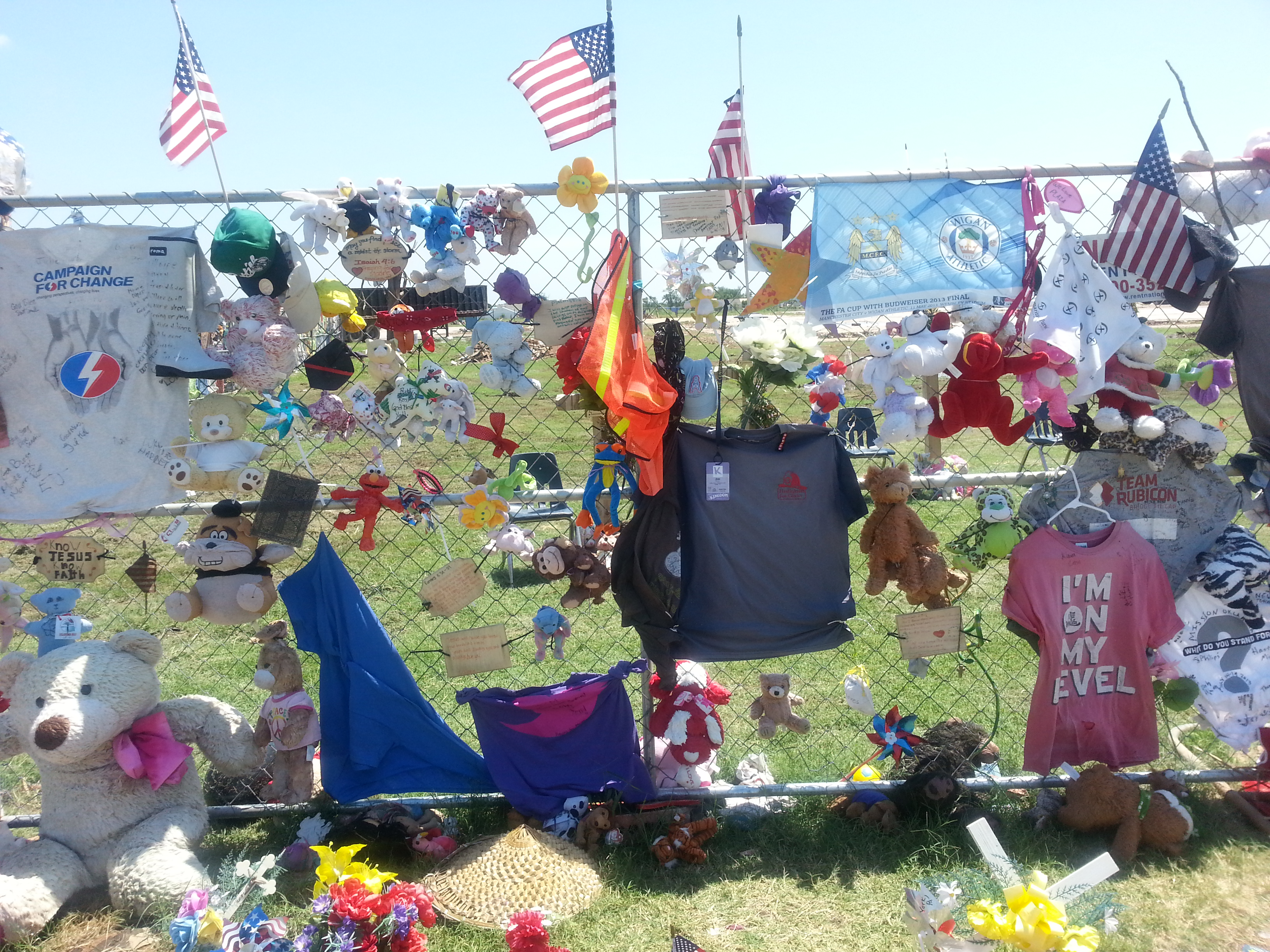 the fence around the school site. So many notes, flags, toys, etc.